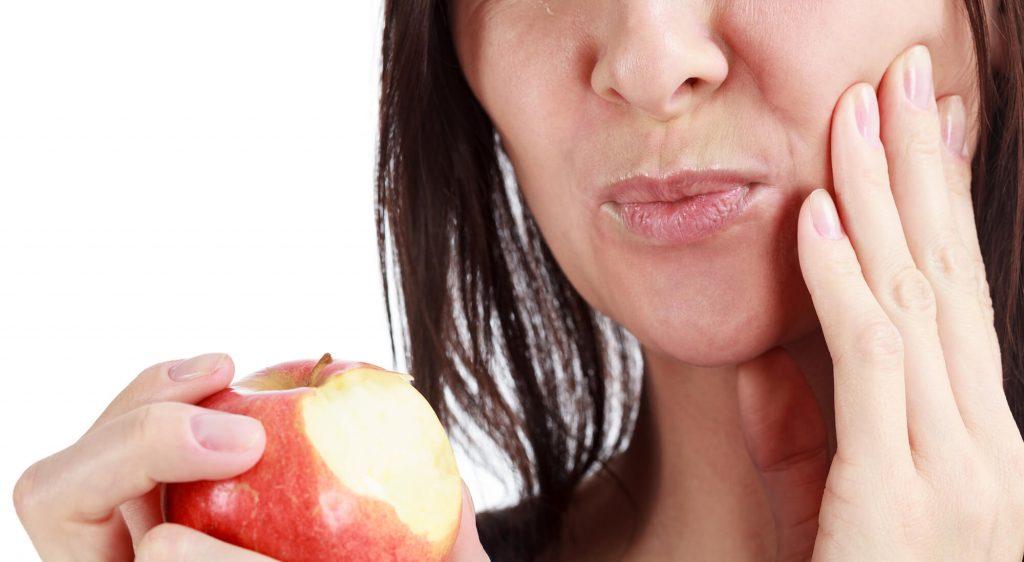 Closeup of a woman biting an apple and needing Naples FL Emergency Dental Care