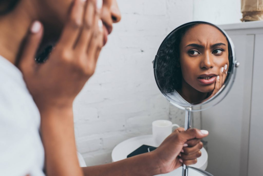 Woman looking in the mirror holding her face needing Naples FL Emergency Dental Care