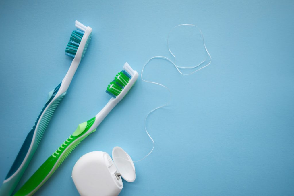 Best Dentist In Naples FL showing the right floss and toothbrush to use